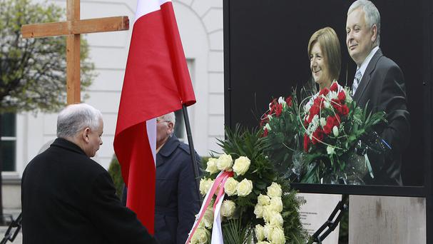 Jaroslaw Kaczynski lays a wreath in front of the portrait of his late twin brother, the former president Lech Kaczynski, and his wife Maria Kaczynska (AP)