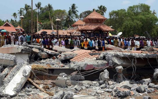 People gather near damaged buildings after a massive fire broke out during a fireworks display at the Puttingal temple complex in Paravoor village, southern Kerala state, India. Photo: AP