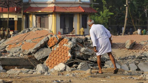 A man checks the damage caused by a massive fire at the Puttingal temple complex in Paravoor in Kerala state, India, in which 116 people died (AP)