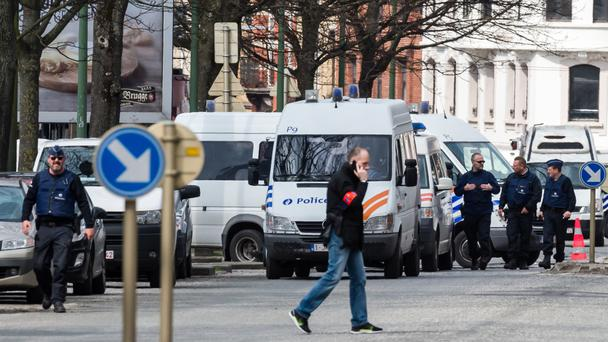 Police secure an area during a house search in the Etterbeek neighbourhood in Brussels (AP)