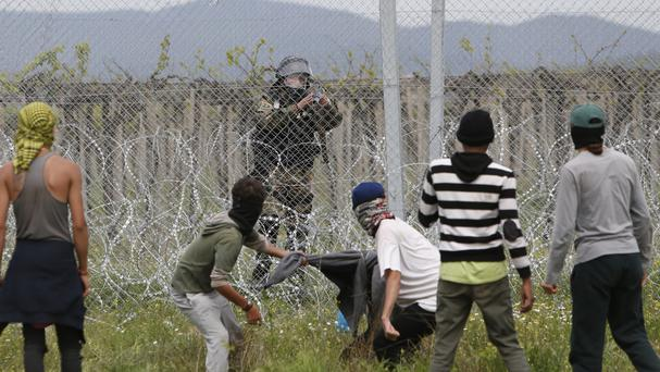 Migrants trying to remove barbed wire along the fence clash with Macedonian police at the northern Greek border point of Idomeni (AP)