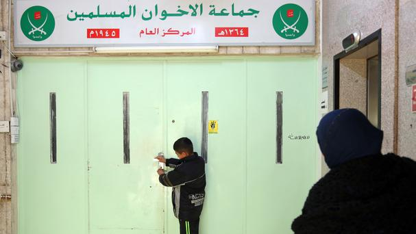 A boy stands at the main entrance of the original Muslim Brotherhood office in Amman, Jordan (AP)