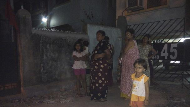 Residents who rushed outdoors following tremors stand on a road outside their houses in Kolkata, India (AP)