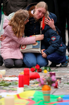 A mother is comforted by her children in Brussels after the March 23 attacks. Top right: German police on guard in Frankfurt Airport (Photos: Christopher Furlong/Getty, AP/Michael Probst)