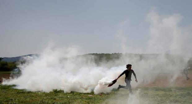 A migrant throws back a tear gas canister during clashes on the Greek-Macedonian border (Reuters/Stoyan Nenov)