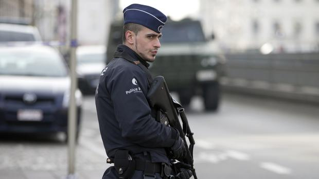 A police officer patrols outside the federal court building in Brussels (AP)