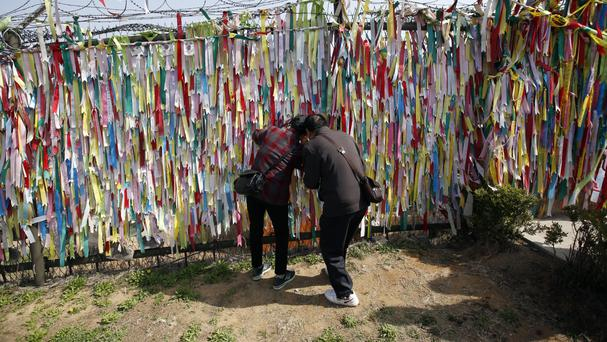 A fence decorated with ribbons with messages urging the reunification of the two Koreas at the Imjingak Pavilion near the border with North Korea (AP)