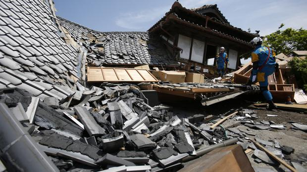 Police rescue team members search damaged houses for trapped people in Mashiki, Kumamoto prefecture after one of a series of earthquakes (AP)