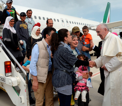 Do this in memory of me: Pope Francis welcomes a group of Syrian refugees after landing at Ciampino airport in Rome Photo: Fillippo Montefori/AP