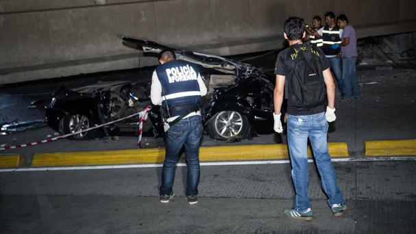 Police look at a car crushed under a collapsed overpass in Guayaquil, Ecuador (AP)