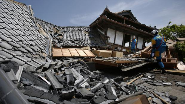 Police rescue teams check for trapped people in collapsed houses in Mashiki after the first earthquake (AP)