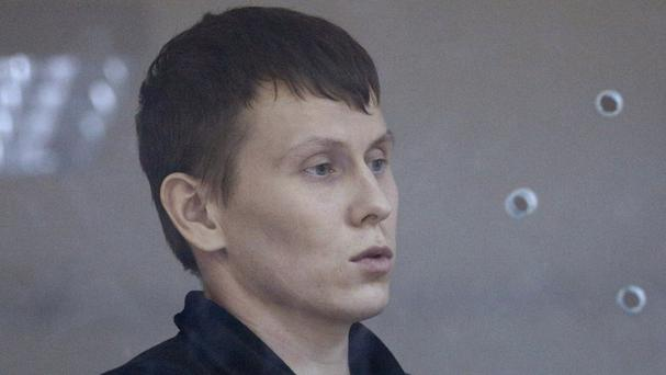 Alexander Alexandrov sits in a cage during court hearings in Kiev, Ukraine (AP)