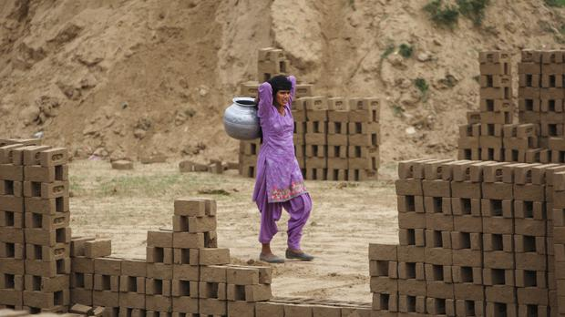 An Indian woman walks with a vessel to fetch water from a canal on the outskirts of Jammu, India, Tuesday, April 19, 2016. Another year of severe drought has left thousands of people without fresh water in at least 13 Indian states, and experts predict the situation will only worsen as summer stretches on. (AP Photo/ Channi Anand)