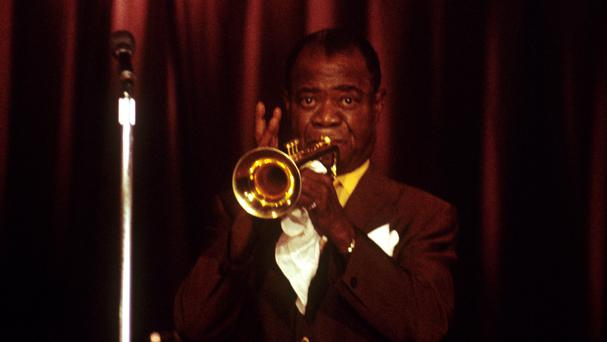 American jazz musician and singer Louis Armstrong in action on his trumpet in Britain