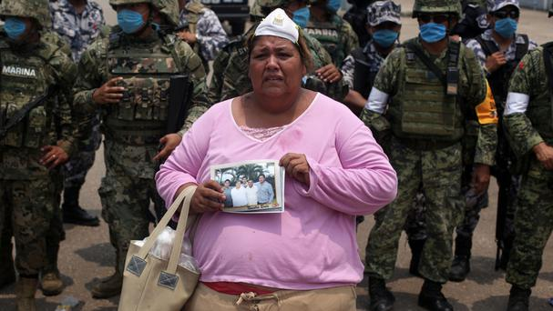 Rosa Villalobos holds a photo of her son Luis Alfonso Ruiz, 25, outside one of the main entrances to the Pajaritos petrochemical complex (AP)