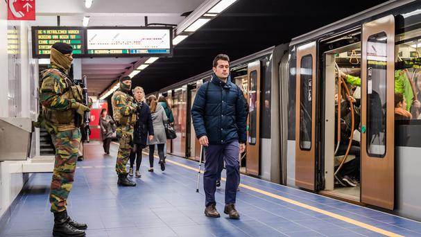 Soldiers patrol as commuters walk on the platform at Maelbeek metro station in Brussels (AP)