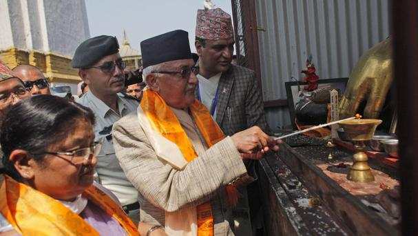 Khadga Prassad Oli lights a butter lamp to initiate reconstruction work at a stupa that was destroyed in last years's earthquake in Kathmandu (AP)