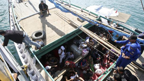 Iranian asylum seekers who were caught in Indonesian waters while sailing to Australia sit on a boat at Benoa port in Bali (AP)