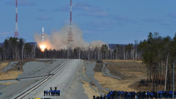 Cosmodrome employees watch the launch of a Russian Soyuz 2.1a rocket at the new Vostochny Cosmodrome (AP)