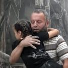 A man carries a child after air strikes hit Aleppo in Syria (Validated UGC/AP)