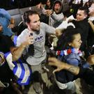 A Trump supporter clashes with protesters outside a rally in California (AP)