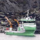 A recovery vessel lifts up parts of the crashed helicopter, off the island of Turoey, near Bergen (AP)