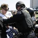 Police officers push back a group protesting against Republican presidential candidate Donald Trump outside of the Hyatt Regency hotel. (AP)
