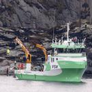 A recovery vessel lifts up parts of the crashed helicopter off the island of Turoey, near Bergen, Norway (AP)