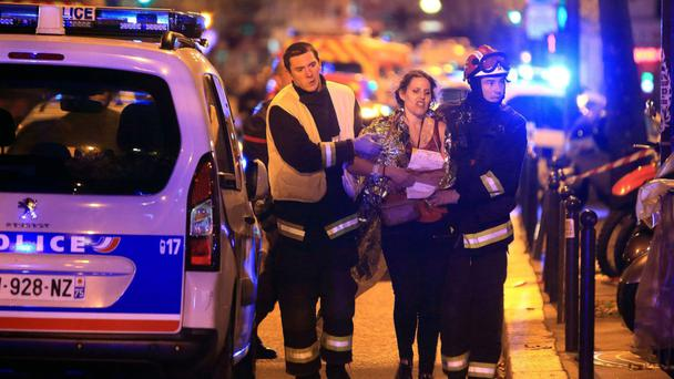ISIL ATTACK: Rescue workers help a woman outside the Bataclan theatre in Paris after last November's murderous attack by Islamic State terrorists. Photo: Thibault Camus/AP