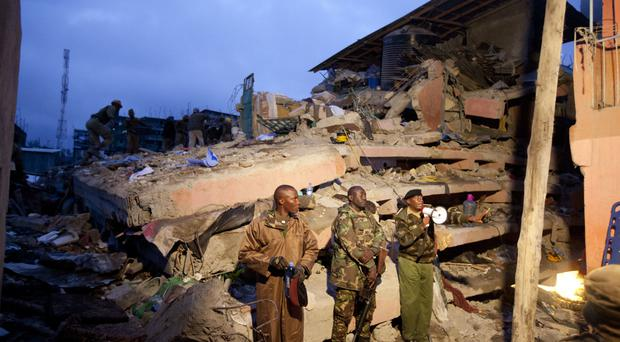 Police officers stand guard at the site of a building collapse in Nairobi
