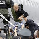 Gerson Galvez shouts at the press as he is escorted by police officers into a Peruvian Air Force plane, in Bogota, Colombia (AP)