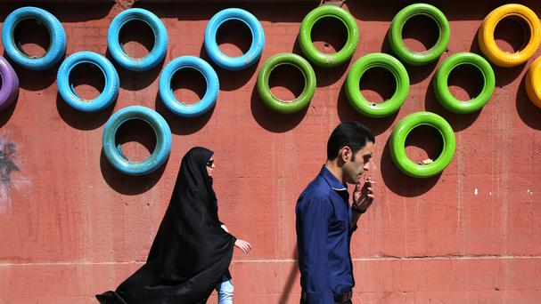 Two Iranians walk past a decorated wall in a pavement in Tehran (AP)