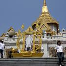 Visitors walk around the Wat Traimitr Withayaram temple in Bangkok, which has become a venerated site for Leicester City fans after a monk predicted the club's English Premier League victory (AP)