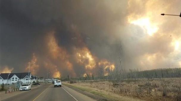 This photo taken through a car windscreen shows smoke rising from a wildfire outside of Fort McMurray, Alberta (Mary Anne Sexsmith-Segato/The Canadian Press via AP)