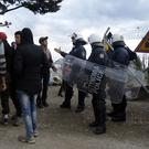 Greek police in riot gear stand near refugees and migrants at the northern border point of Idomeni (AP)