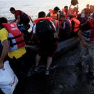 Migrants and refugees in a rubber dinghy arriving on the beach at Psalidi near Kos Town, Kos (AP)