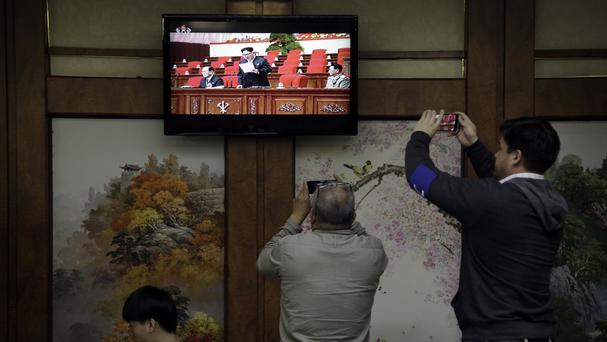 Diners watch a broadcast of the 7th Congress of the Workers' Party of Korea, where North Korean leader Kim Jong Un is seen delivering a speech (AP)
