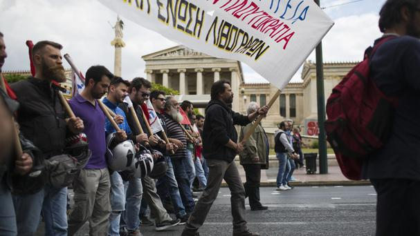 A protester holds a banner while others chant anti-austerity slogans in front of the Athens Academy (AP)