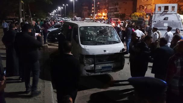 Egyptian people gather around a bullet-ridden vehicle in Cairo (AP)