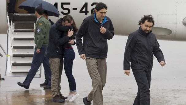 Freed Spanish journalists Antonio Pampliega, background, Jose Manuel Lopez and Angel Sastre, right, arrive at the Torrejon military airbase in Madrid, Spain (Pool Moncloa via AP)