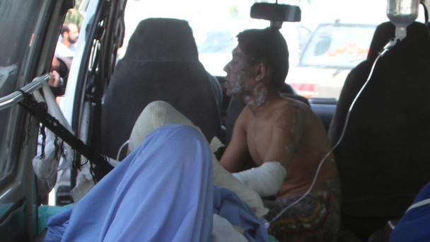 Injured men in an ambulance after an accident on the main highway linking the capital, Kabul, to the southern city of Kandahar (AP)