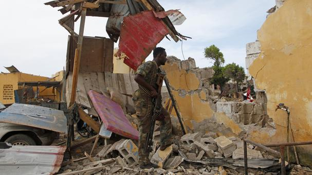 A Somali soldier stands near a destroyed building outside the police traffic station in Mogadishu (AP)