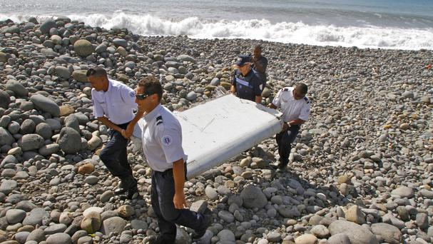 French police officers carry a piece of debris from a plane, known as a flaperon, in Saint-Andre, Reunion Island, the first trace of Malaysia Airlines Flight 370 (AP)
