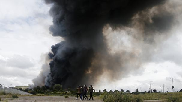Four women walk with masks in front of billowing black smoke from a huge fire in Sesena, central Spain (AP)