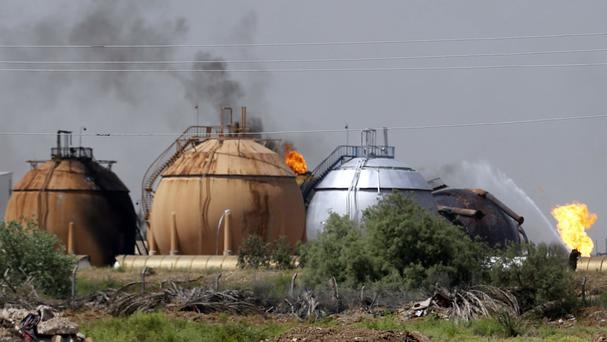 Iraqi firefighters try to extinguish a blaze at a natural gas plant in Taji (AP)