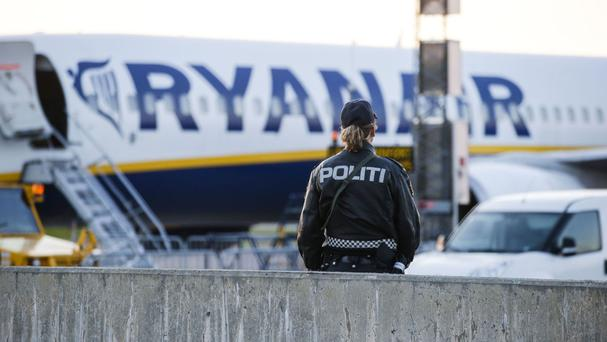 A police bomb officer stands in front of a Ryanair plane at Moss Airport Rygge, Norway (Haakon Mosvold Larsen/NTB via AP)