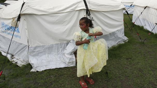 A young girl wears a donated dress at the New Hope shelter set up for people displaced by the earthquake one month ago (AP)