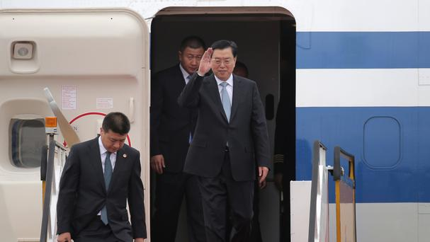 The chairman of China's National People's Congress, Zhang Dejiang, waves as he arrives at Hong Kong's airport (AP)