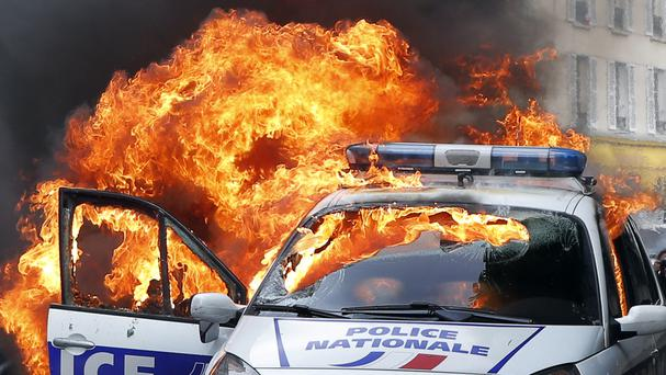 A police car burns during clashes in Paris with protesters (AP)