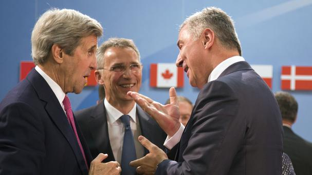 Montenegro's prime minister Milo Dukanovic, right, speaks with US Secretary of State John Kerry, left, and Nato secretary-general Jens Stoltenberg in Brussels (AP)